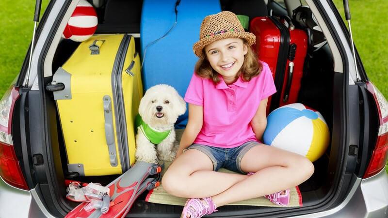 Mädchen mit Strohhut und Hund sitzen in einem vollgepackten Kofferraum