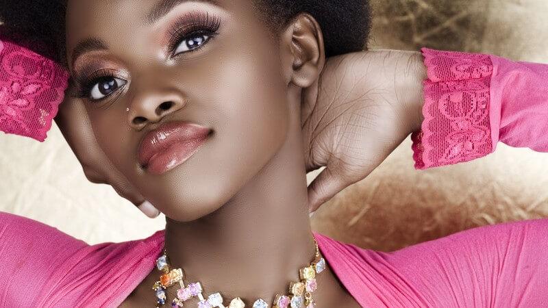 Dunkelhäutiges Model mit Halskette im pinken Top
