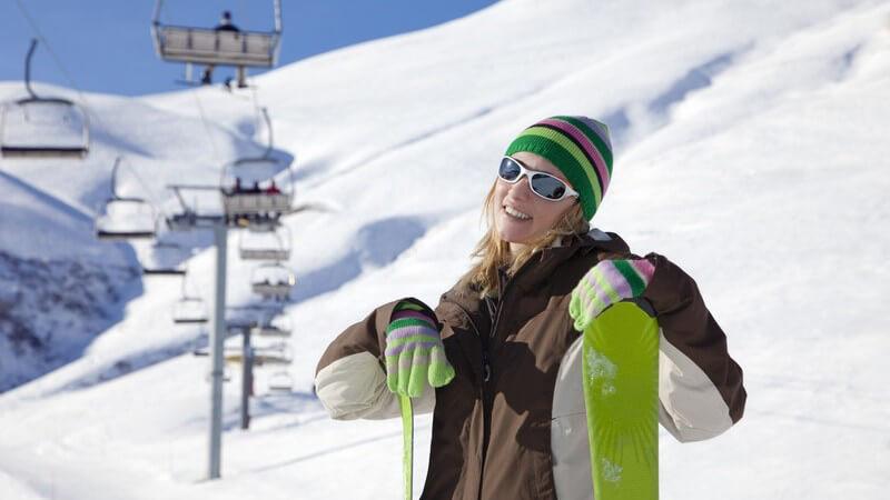 Junge Frau mit Skiern, im Hintergrund Piste und Lift