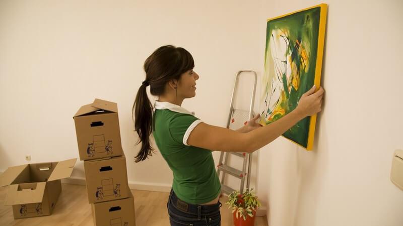 Frau hängt Bild in neuer Wohnung an die Wand
