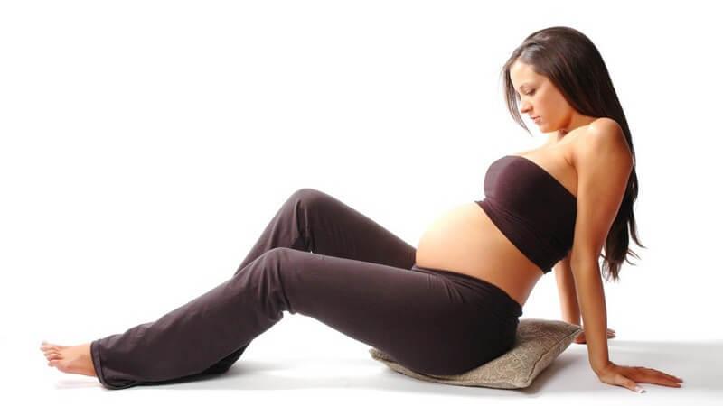 Schwangere Frau in Trainingshose und Top sitzt auf Kissen, weißer Hintergrund