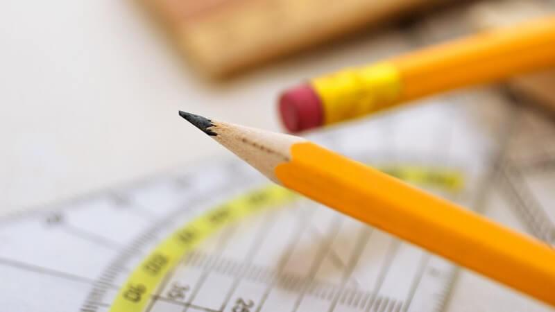 Geodreieck und zwei orange-gelbe Bleistifte