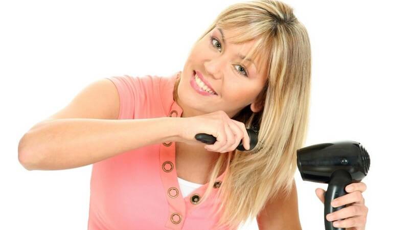 Haarpflege - Frau fönt und bürstet ihr blondes Haar