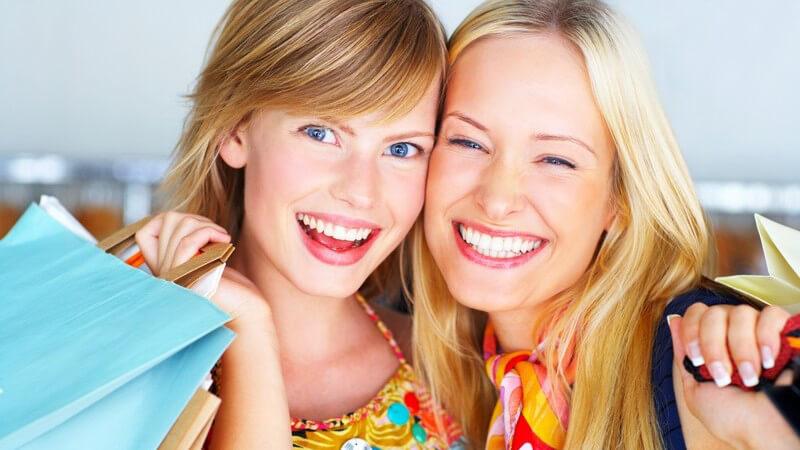 Zwei Freundinnen mit Einkaufstaschen nach Shopping, lachen in die Kamera