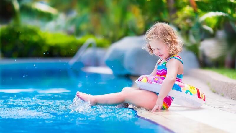 Kleines Mädchen sitzt mit buntem Schwimmreifen am Beckenrand und plantscht mit den Füßen im Wasser