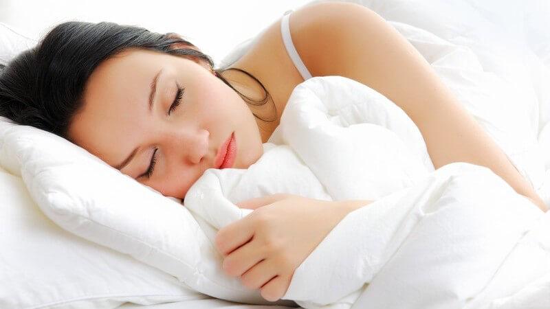 Dunkelhaarige, schlafende Frau in weißer Bettdecke liegend
