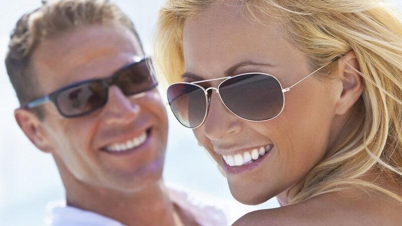 Junges braun gebranntes Paar mit Sonnenbrillen am Strand