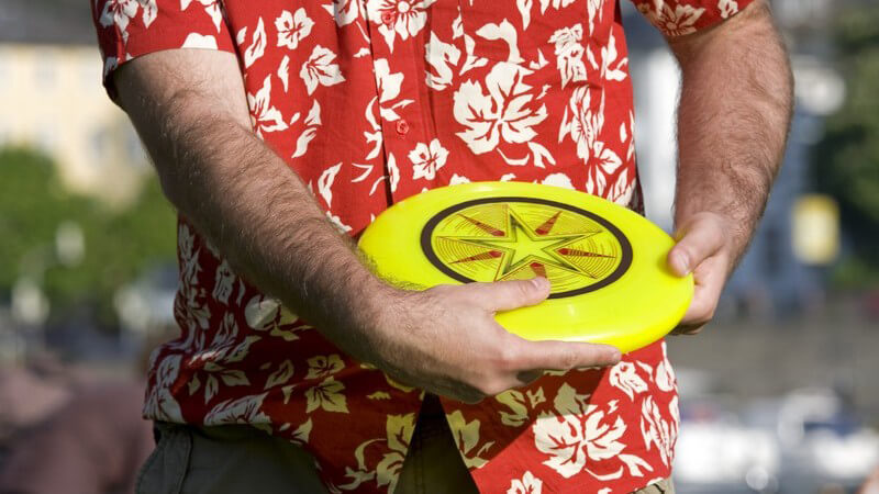 Mann im rot-weißen Hawaii-Hemd ist im Begriff, ein gelbes Frisbee zu werfen