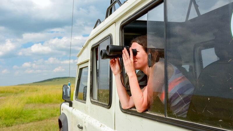 Frau schaut während einer Safari durch ein Fernglas aus dem Geländewagen