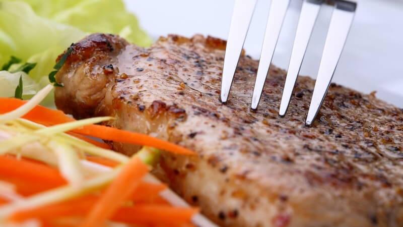 Gabel auf einem Steak und etwas roter und grüner Salat