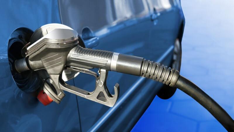 Zapfhahn hängt in Tanköffnung eines blauen Autos