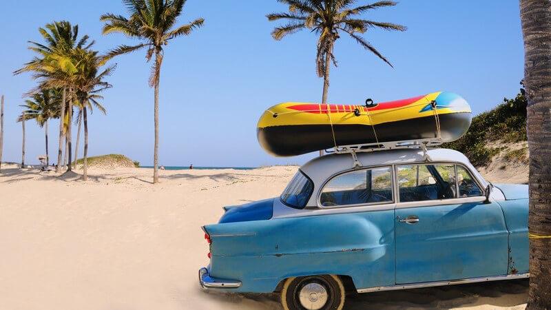Blauer Oldtimer mit Gummitboot auf Dach parkt am Palmenstrand
