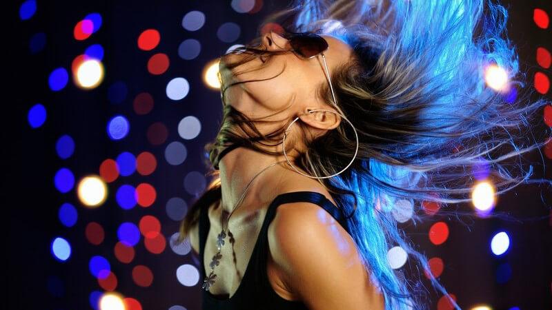 Seitenansicht junge Frau wirft beim Tanzen Kopf nach hinten