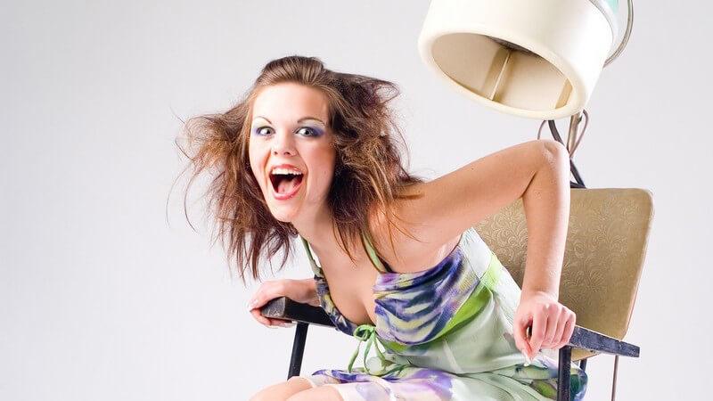 Junge Frau sitzt auf Stuhl unter Trockenhaube, nach vorn gelehnt, Mund offen, zerzauste Haare