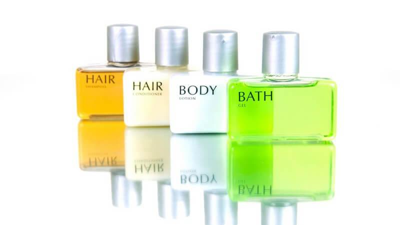 Vier Fläschchen mit verschiedenen Pflegeprodukten für Haut und Haare