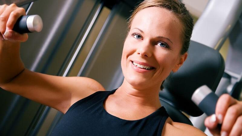 Hellbrünette Sportlerin trainiert ihre Arme im Fitnessstudio und lächelt in die Kamera