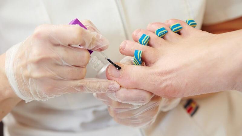 Lackieren der Fußnägel im Kosmetikstudio, zwischen den Zehen hängen blau-gelbe Zehenspreizer