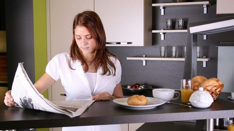 Junge Frau am Küchentisch liest Zeitung, neben ihr Frühstück