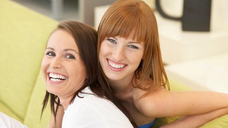 Zwei lachende Frauen sitzen auf der Couch