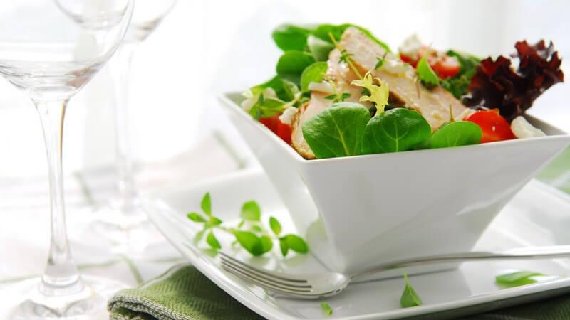 Salat mit Hähnchenstreifen in hoher, quadratischer Schale mit Unterteller und grüner Serviette