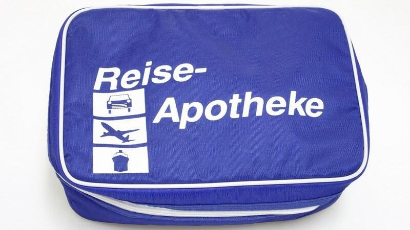 """Blaue Tasche mit Schrift """"Reise-Apotheke"""" und Bildern von Auto, Flugzeug und Schiff"""