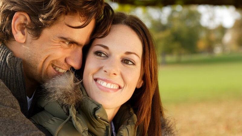 Junges Paar im Herbst im Park, er umarmt sie von hinten