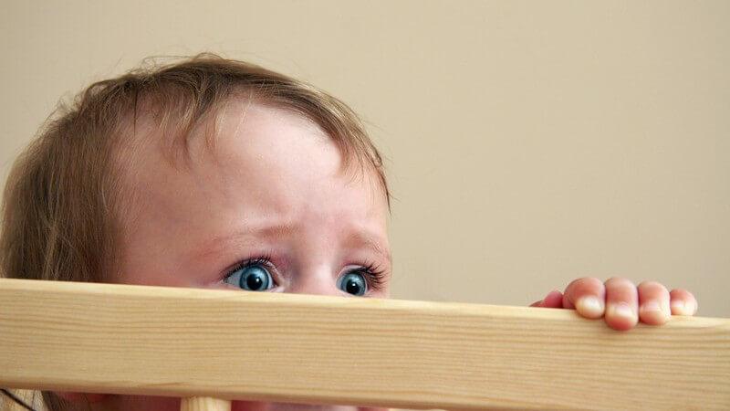 Kleinkind schaut mit ängstlichen Augen über Laufstall