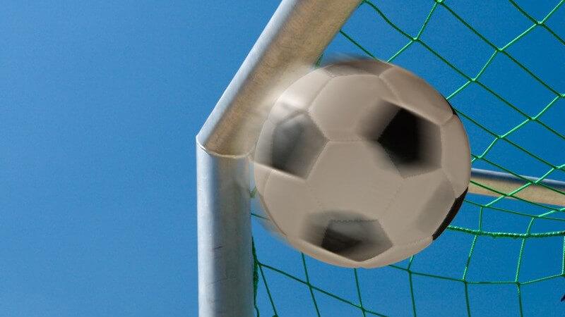 Schwarz-weißer Fußball in linker oberer Torecke fliegend
