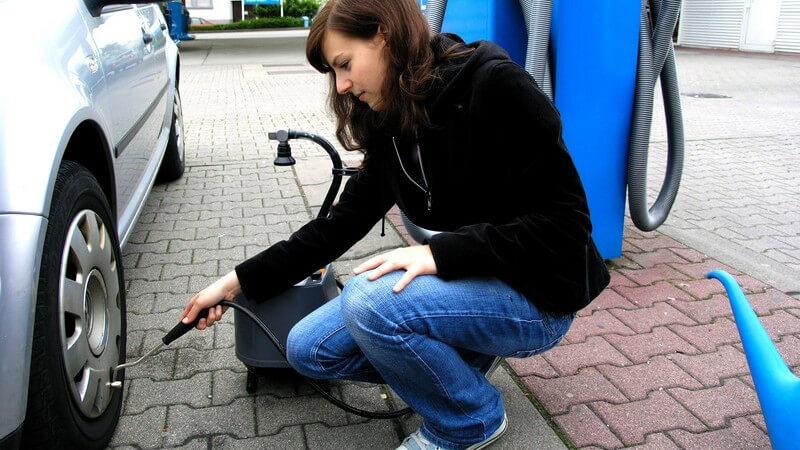 Junge Frau misst Reifendruck ihre Autos an Tankstelle