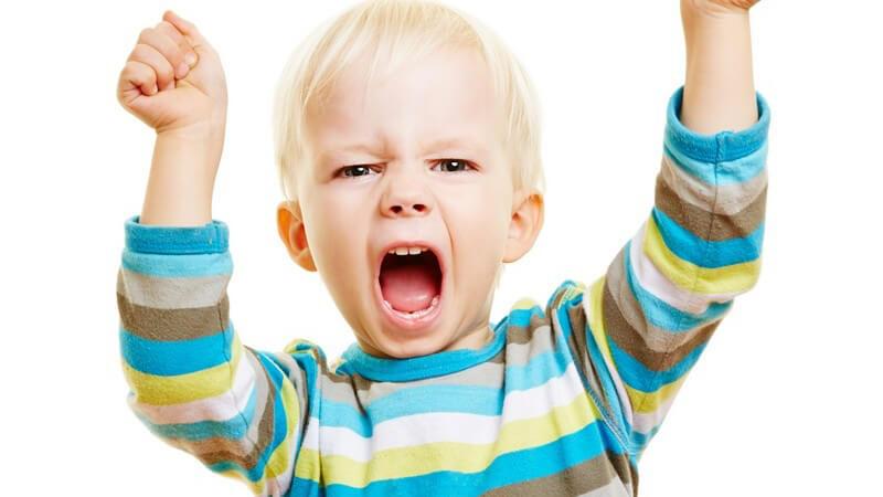 Hellblonder Junge in blau-grünem Streifenpullover guckt verägert und reißt die Arme mit geballten Fäusten hoch