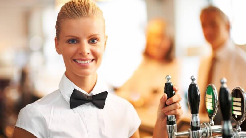 Junge Kellnerin mit Fliege vor Zapfanlage, lächelt in Kamera