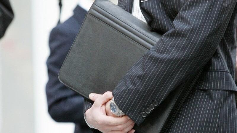 Geschäftsmann mit Aktentasche unter dem Arm, im Hintergrund eine Frau