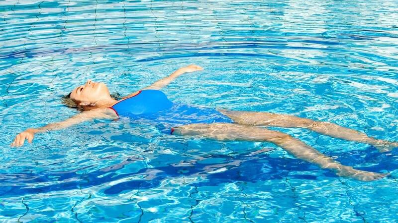 Junge Frau in blauem Badeanzug im Schwimmbad lässt sich auf Rücken im Wasser treiben