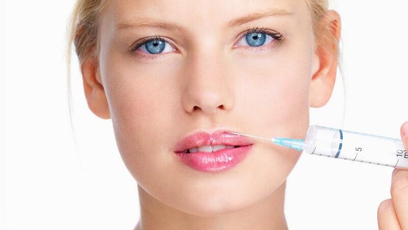 Junge Frau hält eine Botox Spritze an ihre Lippen