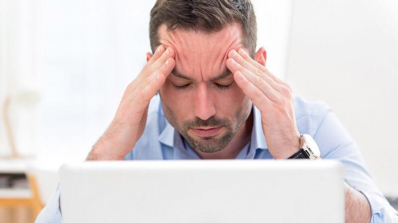 Geschäftsmann in blauem Hemd sitzt vor weißem Laptop und fasst sich vor Kopfschmerzen an die Stirn