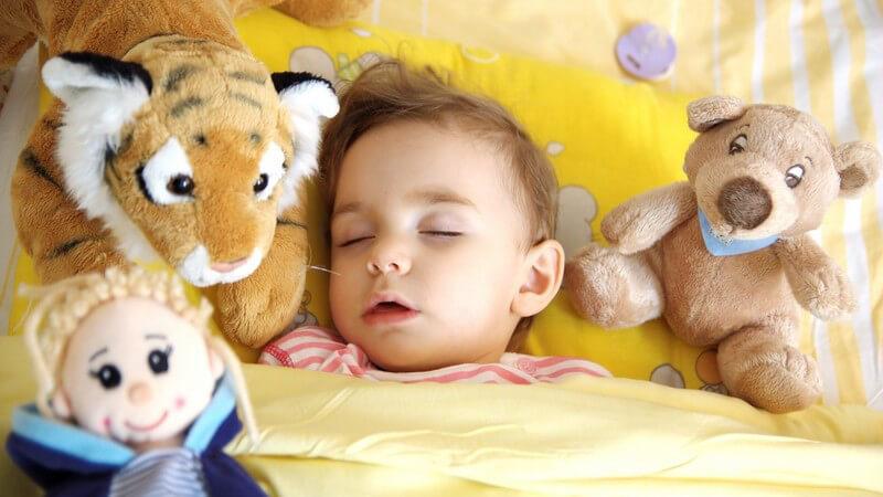 Kleinkind liegt im Bett und schläft, umgeben von Kuscheltieren