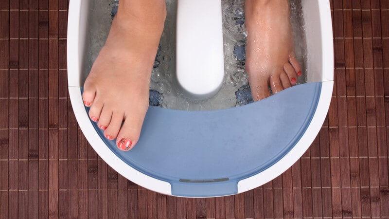 Frauenfüße im sprudelnden Fußbad