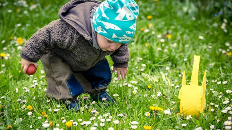 Kleinkind in grauer Jacke und blauer Mütze beim Suchen der Ostereier auf blühender Wiese