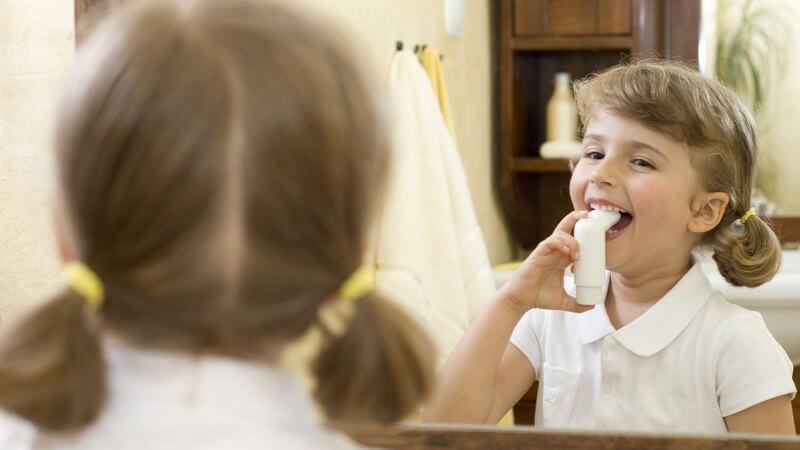 Kleines Mädchen inhaliert vor Spiegel, Asthma