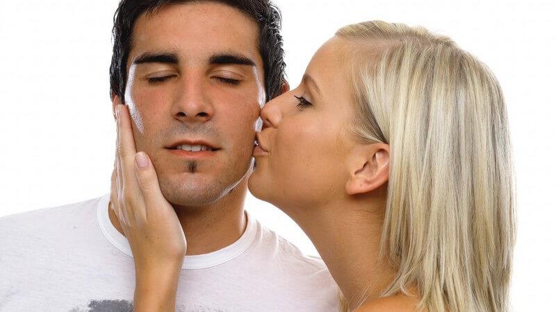 Junge Frau küsst ihren Freund auf die Wange