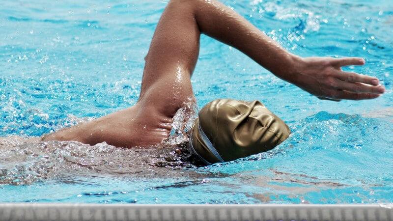 Schwimmer bei Kraulen im Schwimmbad mit goldener Badekappe, Gesicht im Wasser, linker Arm oben