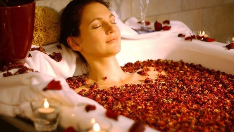 Frau mit geschlossenen Augen in Badewanne mit Kerzen und Sektglas beim Rosenblütenbad mit Rosenblättern