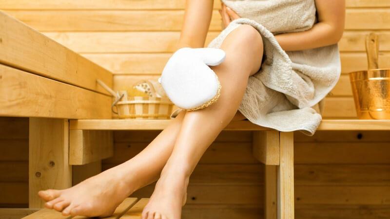 Frau sitzt in der Sauna und massiert ihr Bein mit einem Massagehandschuh