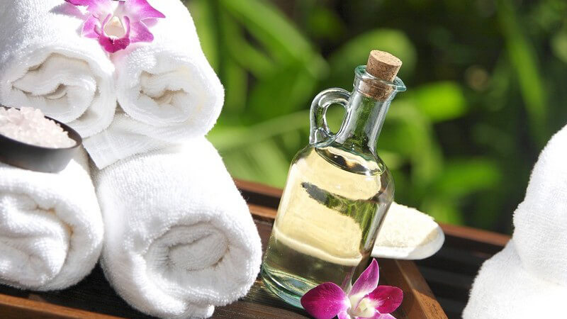 Glasflasche mit Massageöl, weiße zusammengerollte Handtücher auf Holztisch