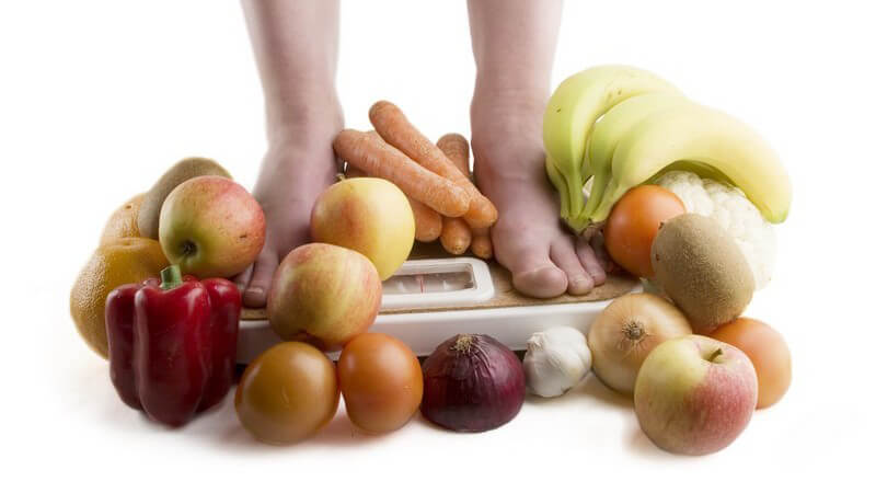 Abnehmen - Füße auf der Waage, umgeben von Obst und Gemüse