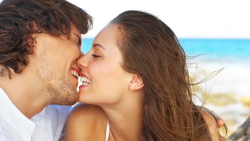 Junges, lächelndes Paar küsst sich am Strand