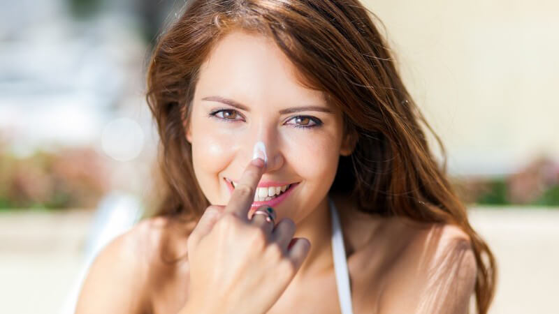 Hübsche braunhaarige Frau tupft sich mit dem Zeigefinger Sonnencreme auf die Nasenspitze