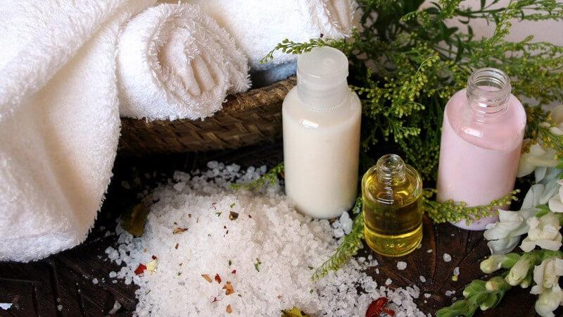 Badesalze, Öle und Cremes vor Kräutern und aufgerollten, weißen Handtüchern im Korb
