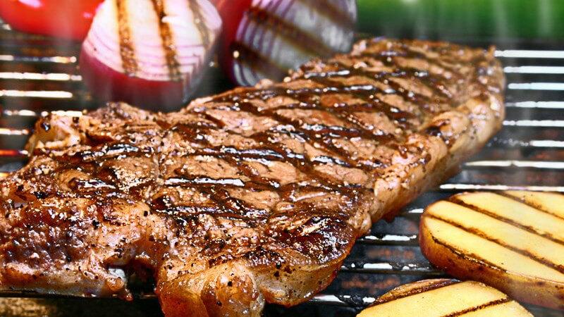 Fertiges Steak auf dem Grill, daneben gegrillte Kartoffelscheiben und Zwiebeln