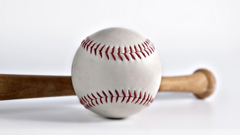 Baseball mit roten Nähten liegt vor Baseballschläger